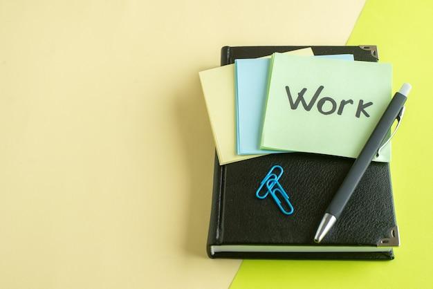 Vorderansicht arbeit geschriebene notiz auf aufklebern mit notizblock und stift auf gelber oberfläche college job schule büro business copybook farbe