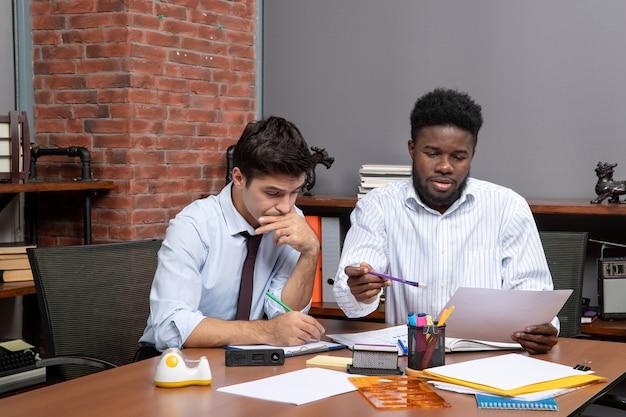 Vorderansicht-arbeitsprozess zwei beschäftigte geschäftsleute, die im büro arbeiten