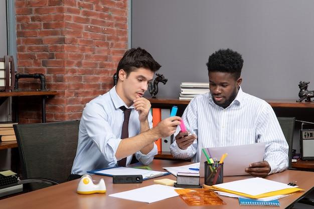 Vorderansicht arbeitsprozess zwei geschäftsleute, die im büro arbeiten working