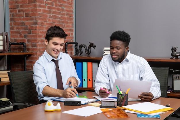 Vorderansicht arbeitsprozess zwei geschäftsleute, die im büro zusammenarbeiten