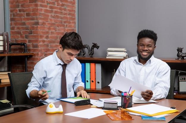 Vorderansicht arbeitsprozess zwei kollegen, die geschäftsverhandlungen in einem modernen büro führen