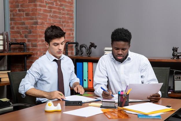 Vorderansicht-arbeitsprozess zwei selbstbewusste geschäftsleute, die im büro arbeiten