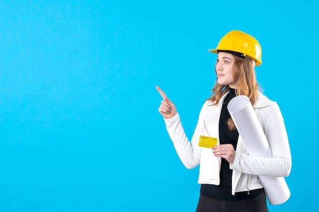 Vorderansicht architektin holding plan und bankkarte auf dem blau