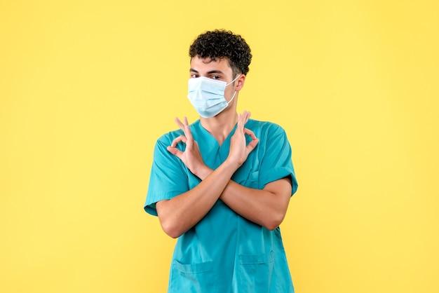 Vorderansicht arzt der arzt in der maske spricht über die medizinischen masken