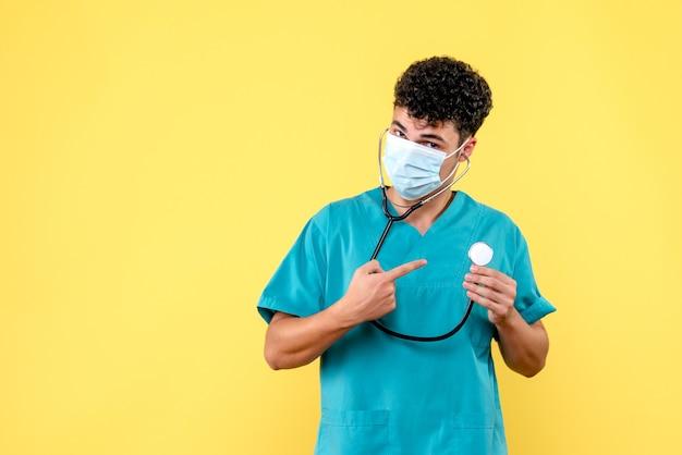 Vorderansicht arzt der arzt in der maske zeigt auf das phonendoskop