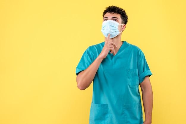 Vorderansicht arzt der arzt in der maske zeigt auf die medizinische maske