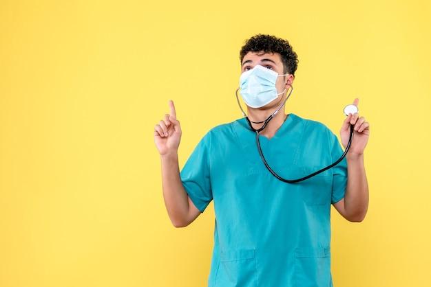 Vorderansicht arzt der arzt in maske mit phonendoskop zeigt nach oben