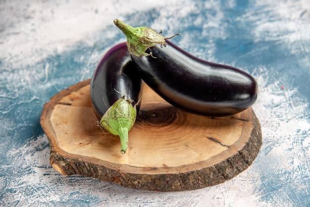 Vorderansicht auberginen auf baumholzbrett auf blau-weiß