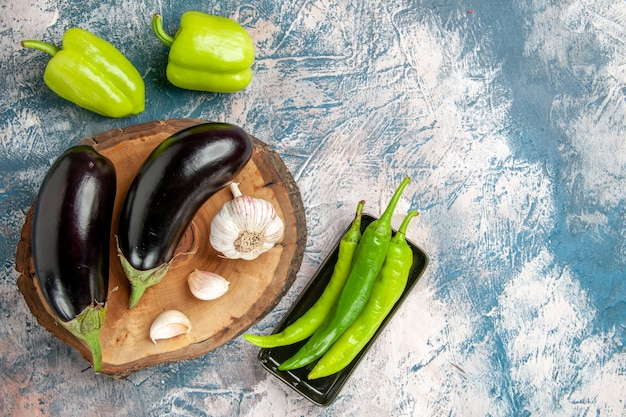 Vorderansicht auberginen knoblauch auf baum holzbrett paprika scharfe grüne paprika auf schwarzem teller pepper