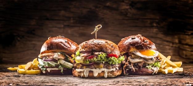 Vorderansicht auf drei große rindfleisch-lachs- und kebab-burger, gefüllt mit frischem gemüsesalat und dressing.