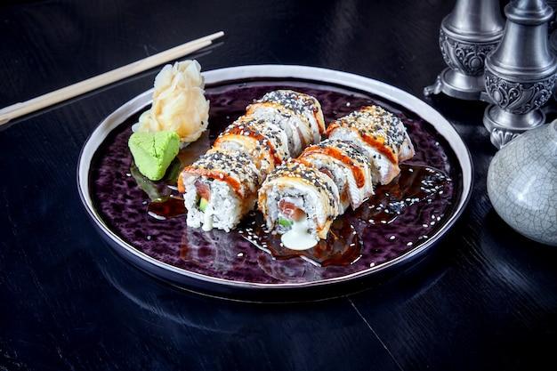 Vorderansicht auf warmem brötchen mit thunfisch, aal und sahne. suchi. japanischer essensstil. meeresfrüchte. gesunde, ausgewogene diät. sushi-rollen auf dunklem teller. kopieren sie platz, lebensmittelhintergrund.