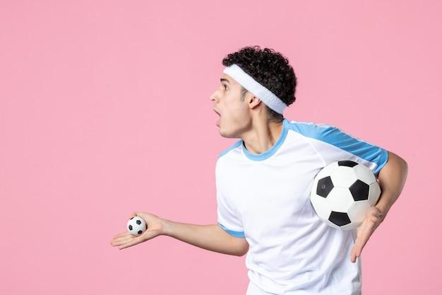 Vorderansicht aufgeregter fußballspieler in sportkleidung mit ball