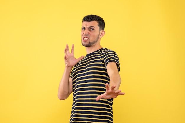 Vorderansicht aufgeregter junger mann im gelb-weiß gestreiften gelben isolierten hintergrund des gestreiften schwarzweiss-t-shirts