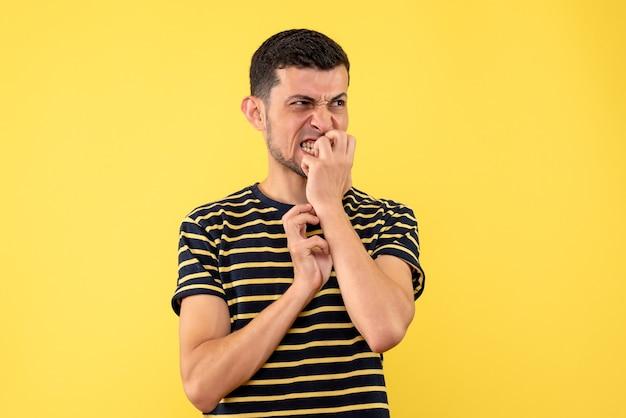 Vorderansicht aufgeregter junger mann im schwarzen und weißen gestreiften gelben isolierten hintergrund des t-shirts