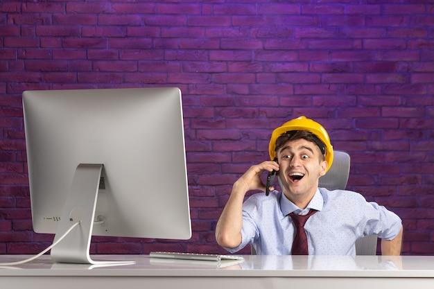 Vorderansicht aufgeregter männlicher konstrukteur hinter dem schreibtisch, der am telefon spricht