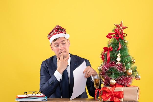 Vorderansicht aufgeregter mann, der am tisch nahe weihnachtsbaum sitzt und auf gelbem hintergrund präsentiert