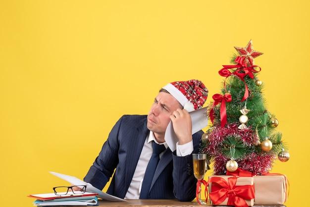 Vorderansicht aufgeregter mann, der an etwas denkt, das am tisch nahe weihnachtsbaum sitzt und auf gelbem hintergrund präsentiert