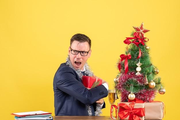 Vorderansicht aufgeregter mann, der sein geschenk versteckt, das am tisch nahe weihnachtsbaum sitzt und auf gelbem hintergrund präsentiert