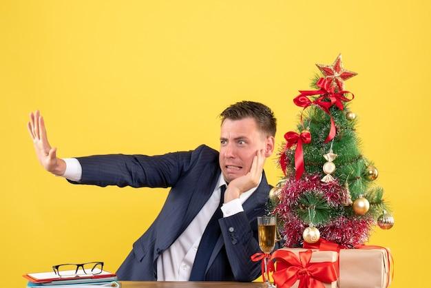 Vorderansicht aufgeregter mann, der versucht, etwas zu stoppen, das am tisch nahe dem weihnachtsbaum und den geschenken auf gelbem hintergrund sitzt