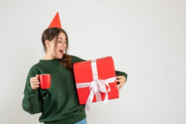 Vorderansicht aufgeregtes mädchen mit partykappe, die ihr weihnachtsgeschenk und eine tasse hält