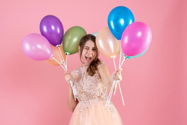 Vorderansicht aufgeregtes partygirl mit partykappe, die luftballons nahe ihrem gesicht hält