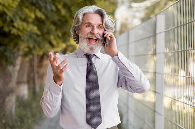 Vorderansicht bärtiger reifer mann, der am telefon spricht
