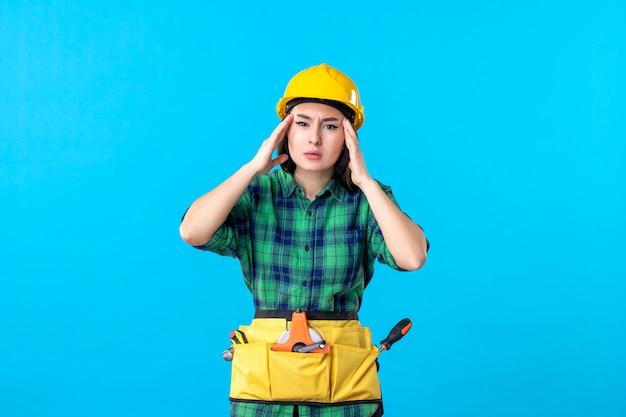 Vorderansicht baumeisterin in uniform mit verschiedenen werkzeugen auf blau