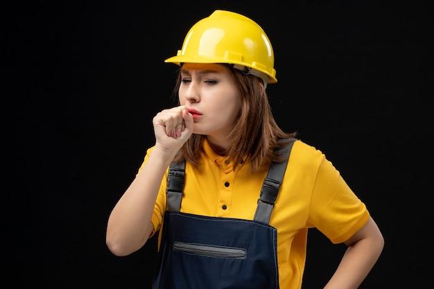 Vorderansicht baumeisterin in uniform und helm an der schwarzen wand