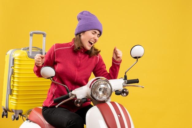Vorderansicht begeisterte junge frau auf moped, die ihr gefühl ausdrückt
