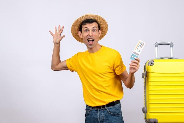 Vorderansicht begeisterte jungen touristen, der nahe gelbem koffer hält, der ticket hält