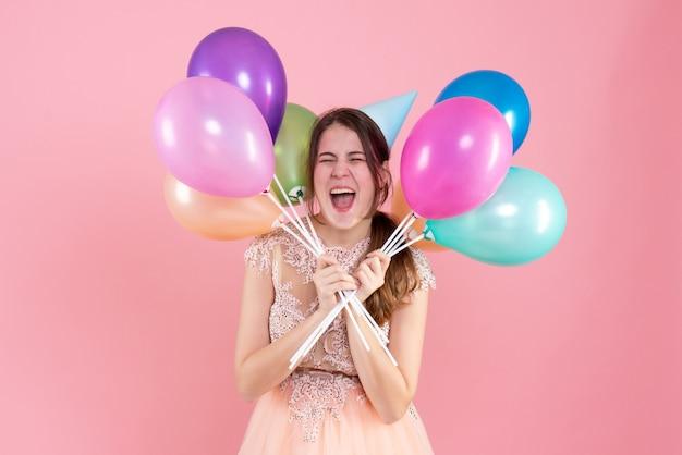 Vorderansicht begeisterte partygirl mit partykappe, die luftballons nahe ihrem gesicht hält