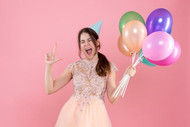 Vorderansicht begeisterte partygirl mit partykappe hält ballons, die fingerpistole machen