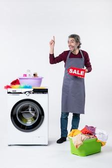 Vorderansicht begeisterter junger mann in schürze, der ein verkaufsschild in der nähe der waschmaschine auf weißem hintergrund hält