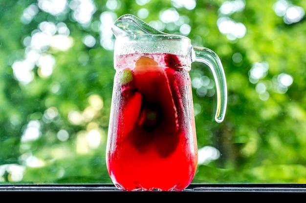 Vorderansicht belebende limonade im dekanter mit zitronenlimette und erdbeere