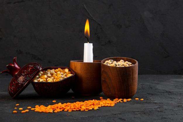 Vorderansicht beleuchtete kerze mit bohnen mais und linsen