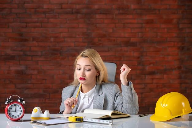 Vorderansicht betonte ingenieurin, die hinter ihrem arbeitsplatz sitzt