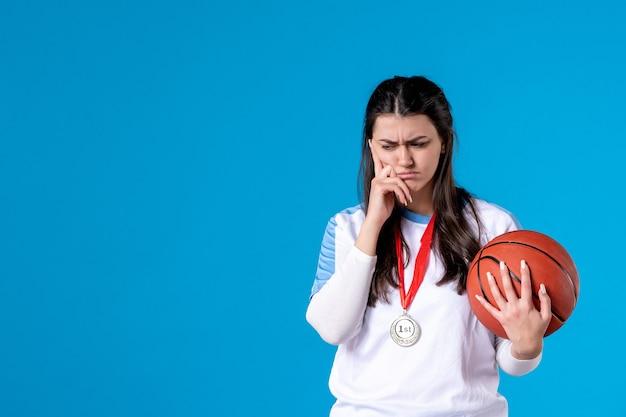 Vorderansicht betonte junge frau, die basketball hält