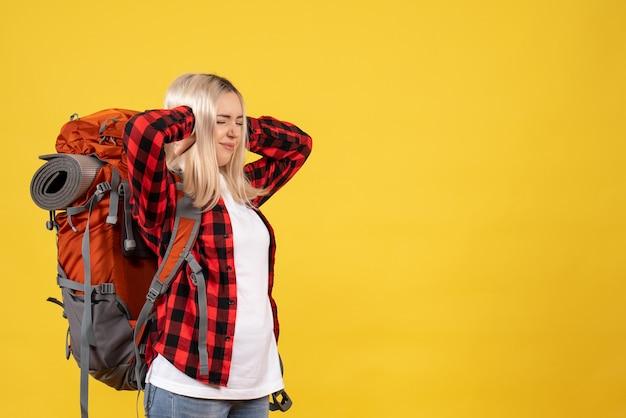 Vorderansicht beunruhigte blondes mädchen mit ihrem rucksack, der ihre ohren mit den händen schließt