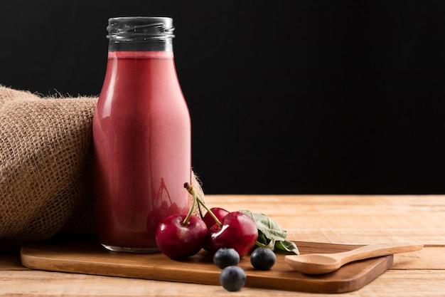 Vorderansicht blaubeeren und kirschen mit smoothie in glasflasche