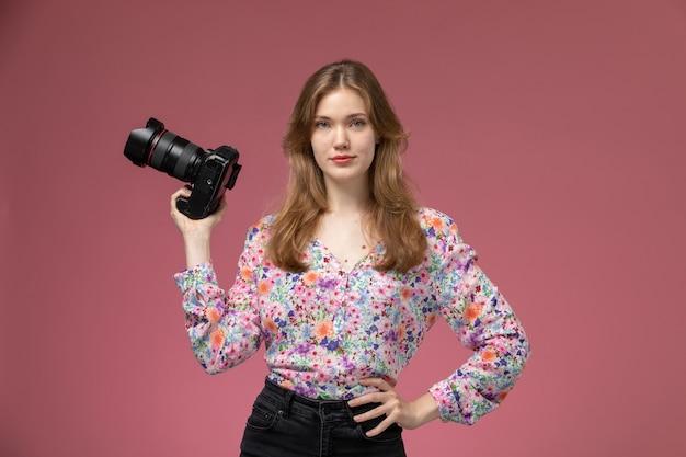 Vorderansicht blonde dame mit ihrer fotokamera auf ihrer rechten hand