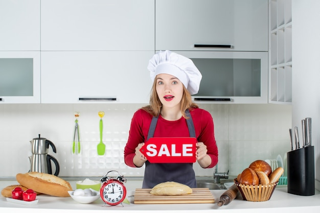 Vorderansicht blonde hübsche frau in kochmütze und schürze mit verkaufsschild in der küche