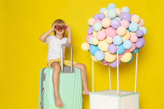 Vorderansicht blonder junge im weißen t-shirt, das auf dem grünen wasserbeutel zusammen mit den mehrfarbigen luftballons auf dem gelben boden sitzt