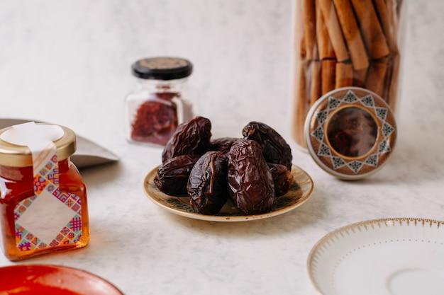 Vorderansicht braune xurma süß lecker zusammen mit verschiedenen sachen auf dem weißen boden
