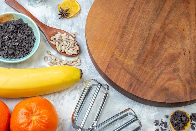 Vorderansicht brauner holzschreibtisch mit früchten eiern rohem getreide und samen auf weißem hintergrund teigkuchen samen fruchtfarbe hühneraugen kuchenmilch kochen