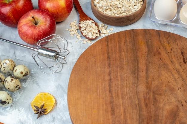 Vorderansicht brauner holzschreibtisch mit früchten eiern rohem getreide und samen auf weißem hintergrund teigkuchen samen fruchtfarbe maiskoch kuchen milch
