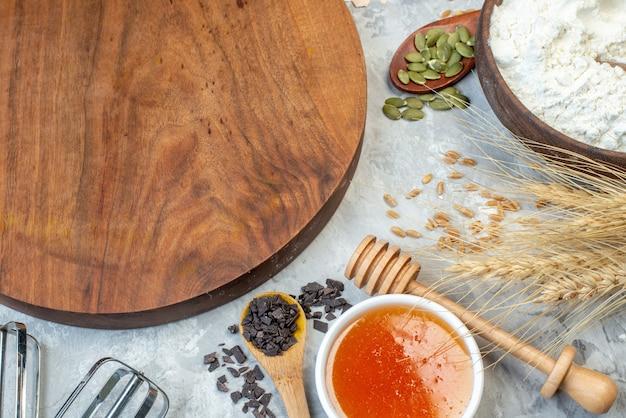 Vorderansicht brauner holzschreibtisch mit früchten eiern rohem getreide und samen auf weißem hintergrund teigkuchen samenfarbe maiskochkuchen milch