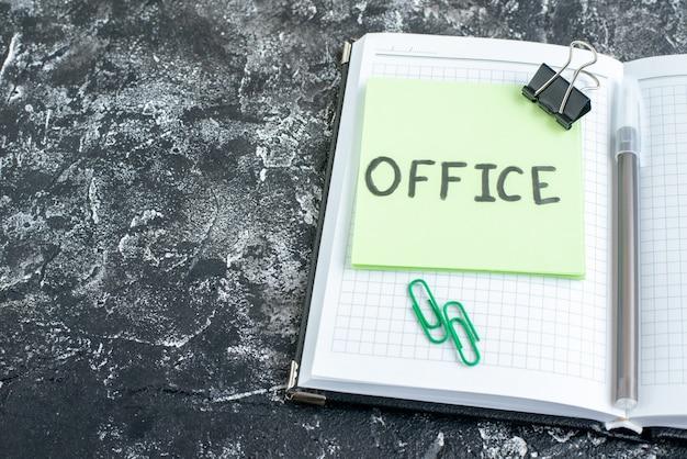 Vorderansicht büro schriftliche notiz mit heft und stift auf grauer oberfläche farbe job college-büro fotoarbeit schule business-team