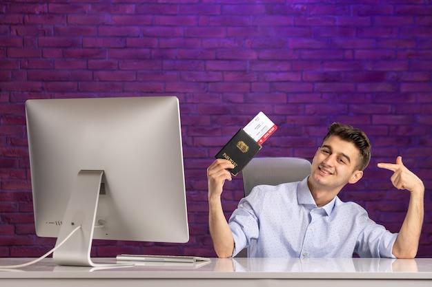 Vorderansicht büroangestellter sitzt hinter seinem arbeitsplatz mit pass und tickets