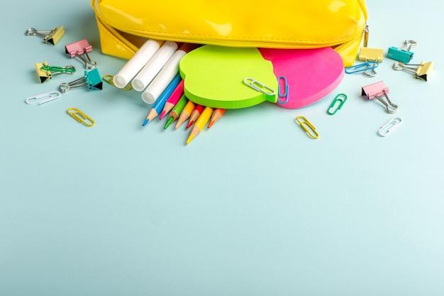 Vorderansicht buntstifte mit aufklebern auf blauem schreibtisch