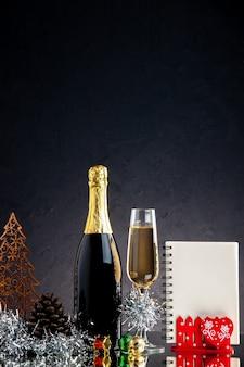 Vorderansicht champagnerglasflasche weihnachtsschmuck notizblock auf dunkler oberfläche